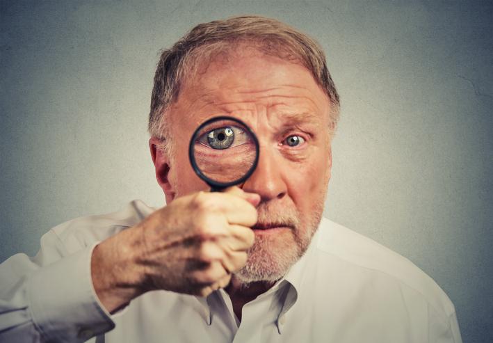 Hombre maduro con una lupa sobre su ojo