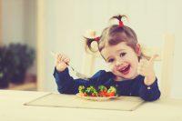 Niña con dos coletas comiendo verdura