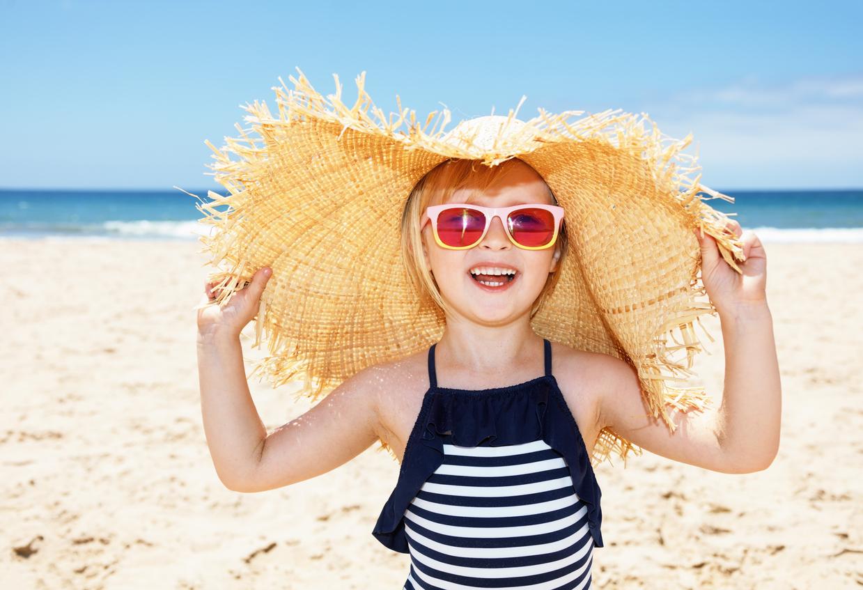 Niña en la playa con gafas de sol y pamela