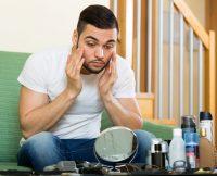 Hombre cuidándose la barba frente a un espejo