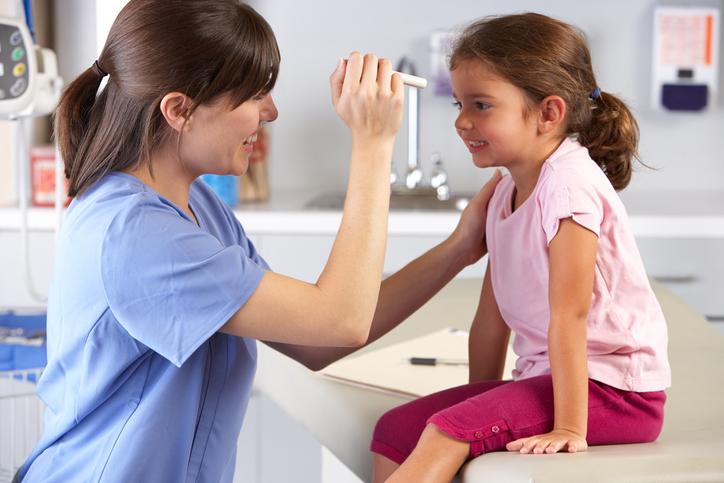 Niña con camiseta rosa durante una revisión oftalmológica