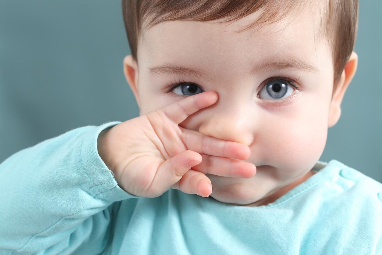 Bebé con los ojos azules se tapa la boca