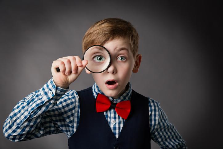 Niño con pajarita mirando por una lupa