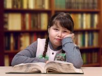 Niña con trenzas leyendo un libro