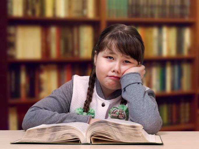 Niña con trenzas frente a un libro
