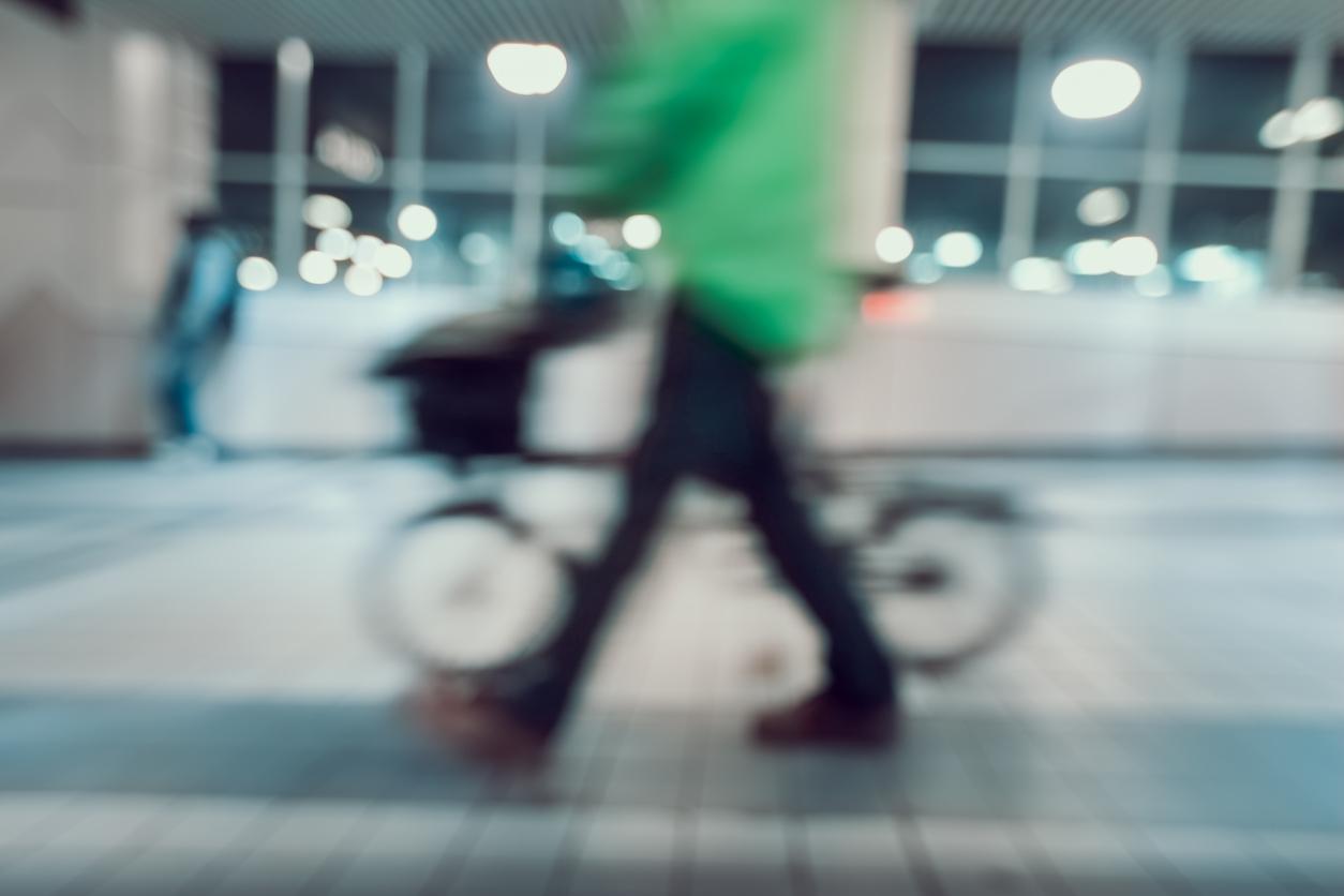 Imagen borrosa de hombre con camisa verde y bicicleta