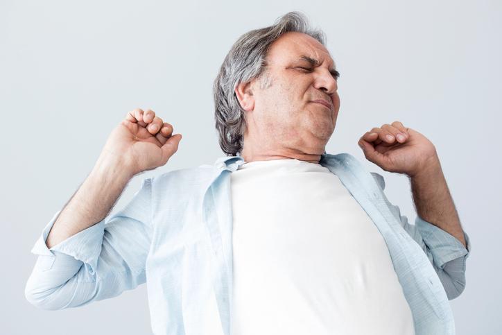 Hombre con camiseta blanca y camisa azul estirándose