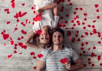 Hombre y mujer tumbadados rodeados de corazones