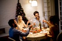 Grupo de amigos cenando en Navidad con bengalas