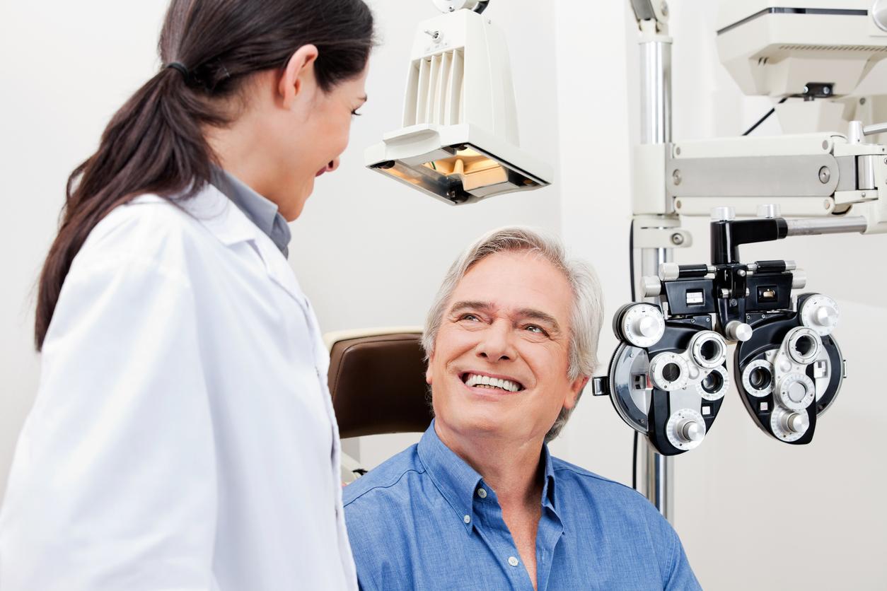 Hombre con camisa azul sonríe al médico en una consulta de oftalmología