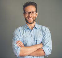 Hombre con camisa azul y gafas cruza los brazos