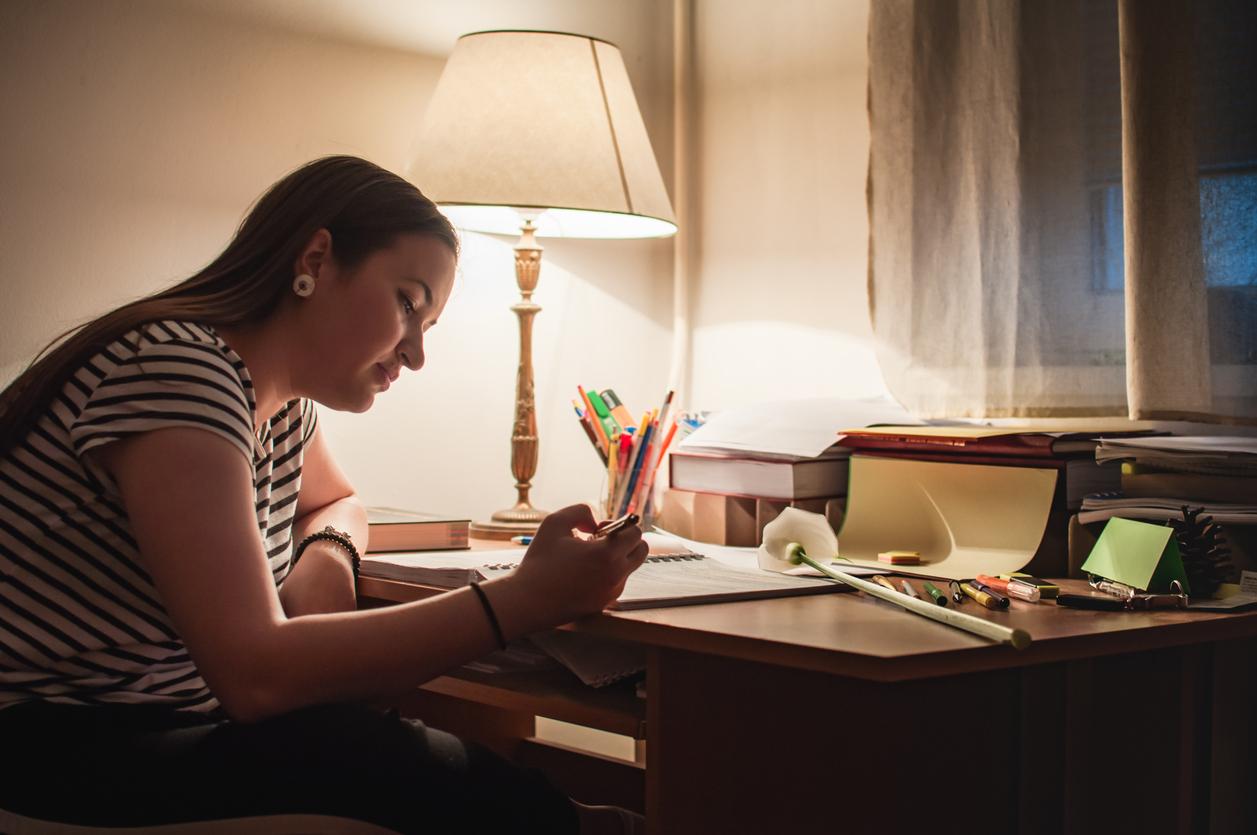 Mujer estudiando a la luz de una lámpara