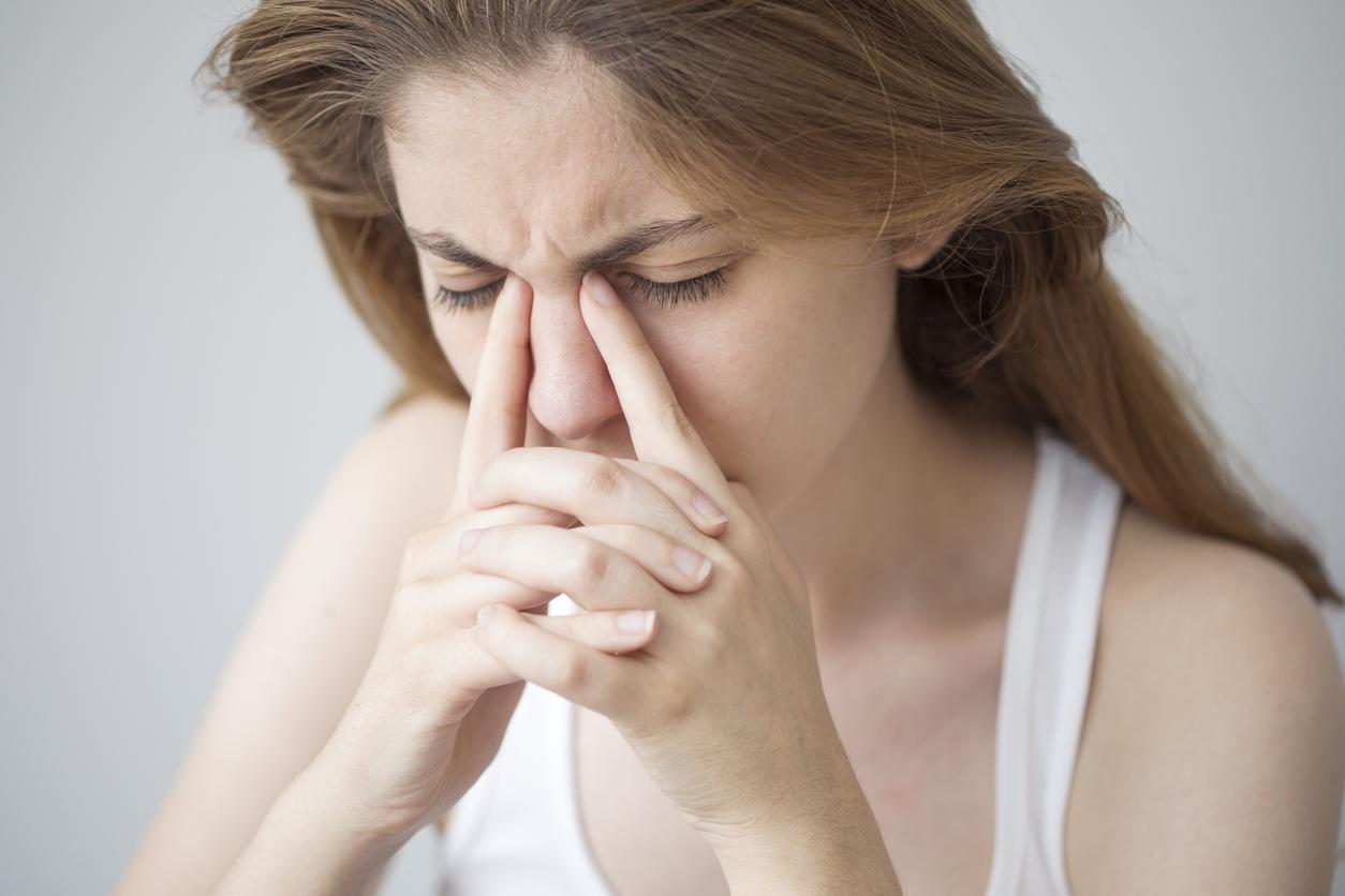 Mujer con camiseta blanca frotándose los ojos
