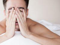 Hombre moreno tumbado en la cama se frota los ojos