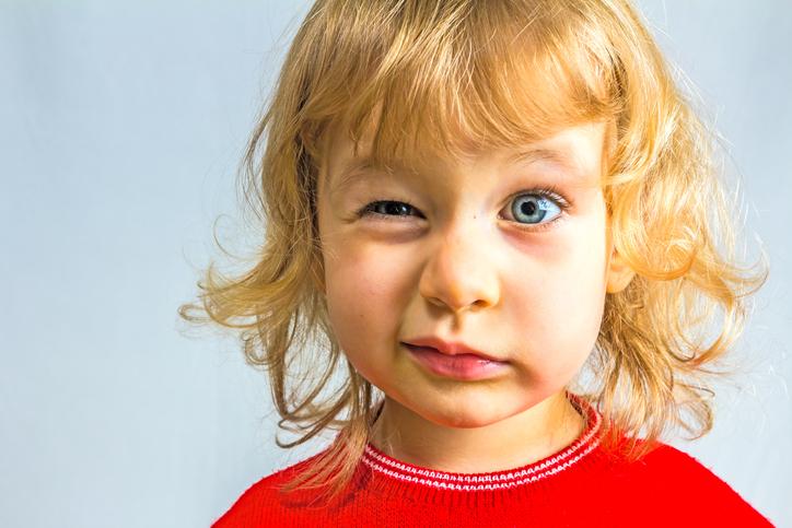 Niño rubio con jersey rojo guiñando un ojo