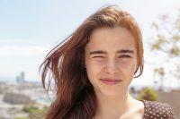 Chica pelirroja con vestido marrón guiñando un ojo