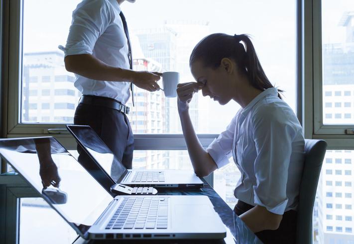 Mujer con camisa blanca se frota los ojos trabajando en una oficina frente al ordenador