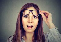 Mujer castaña con cara de sorpresa quitándose las gafas