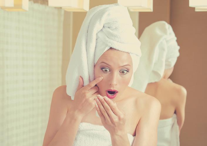 Mujer sorprendida mirándose al espejo