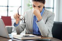Mujer frotándose los ojos mientras trabaja frente al ordenador