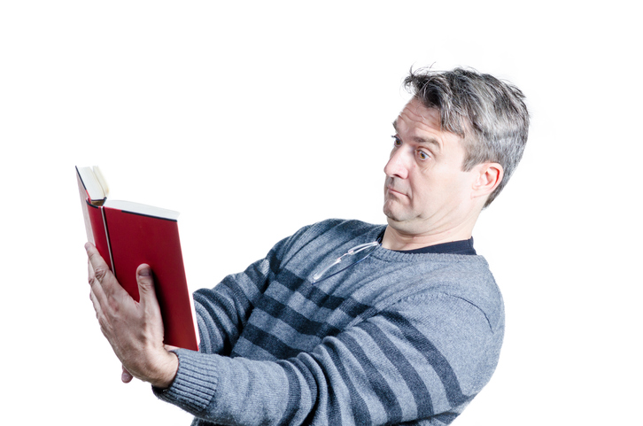 Hombre alejando un libro para leerlo