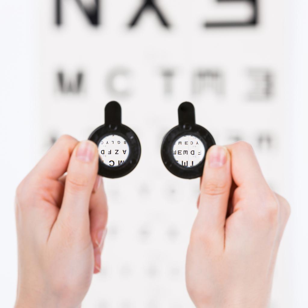Manos sujetando lentes frente a un optotipo