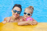 Mujer y niña con gafas de sol en la piscina
