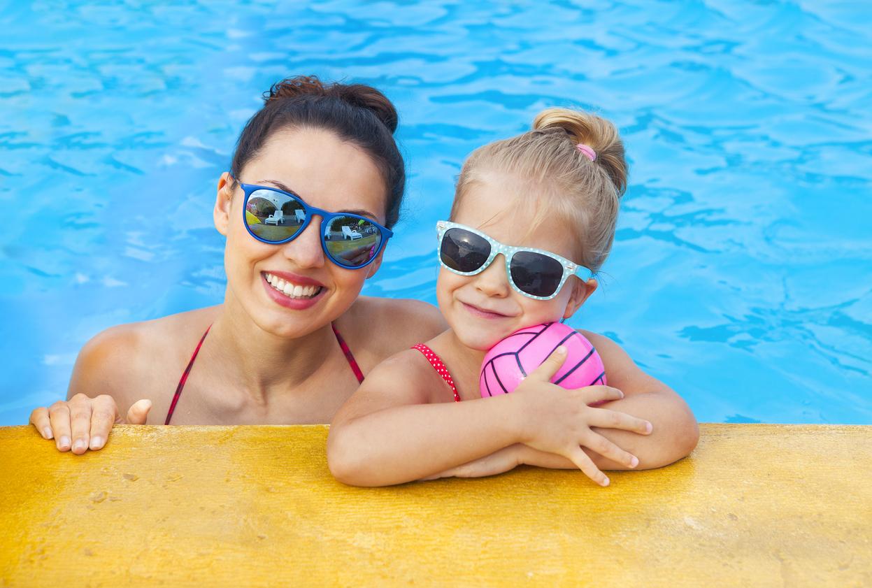 Mujer y niña dentro de la piscina con gafas de sol