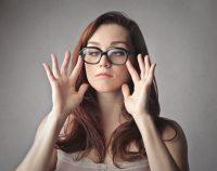 Mujer pelirroja con gafas tuerce los ojos