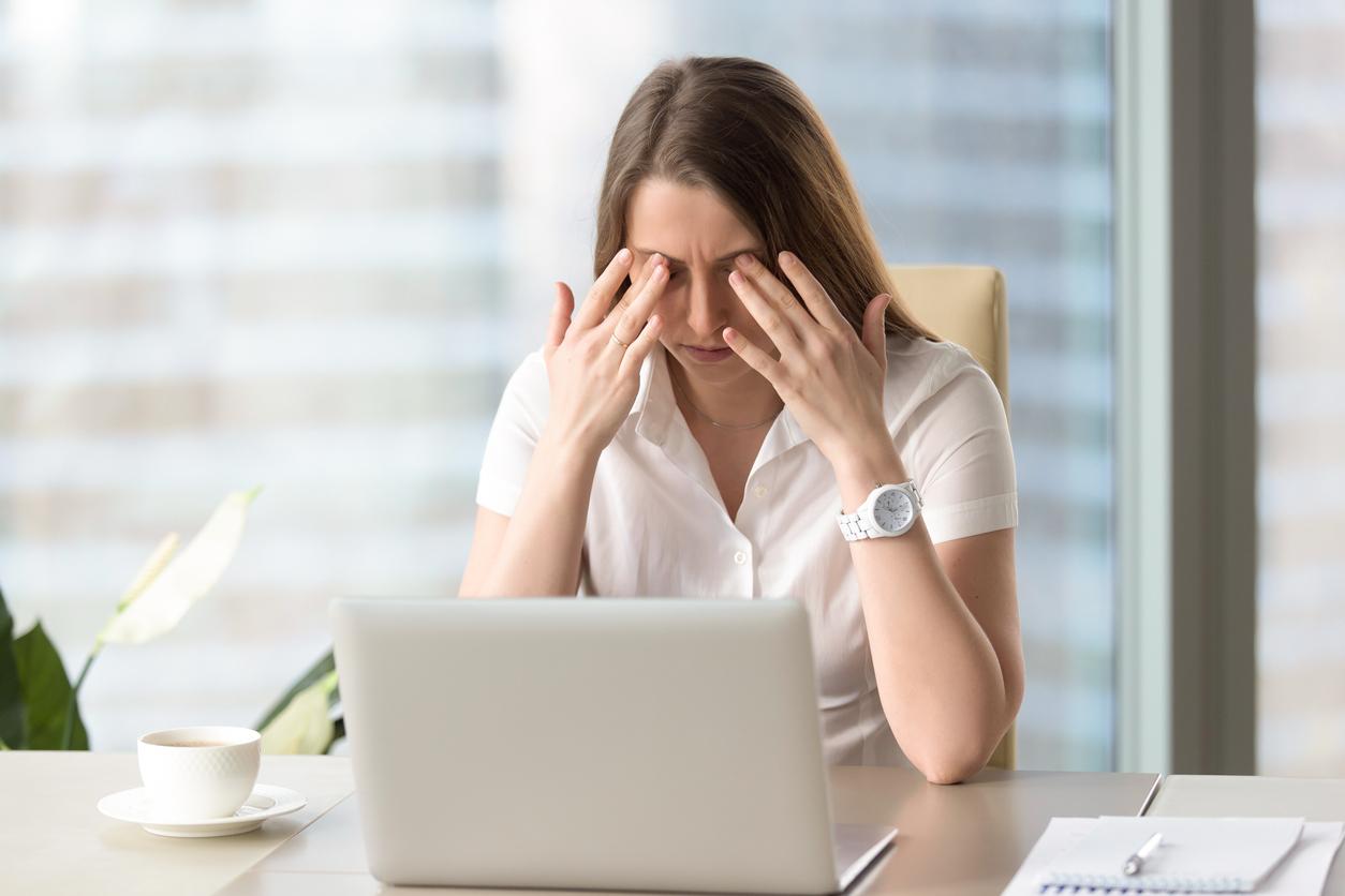 Mujer frotándose los ojos mientras trabaja en un ordenador