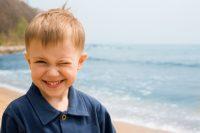 Niño pelirrojo guiña un ojo en la playa