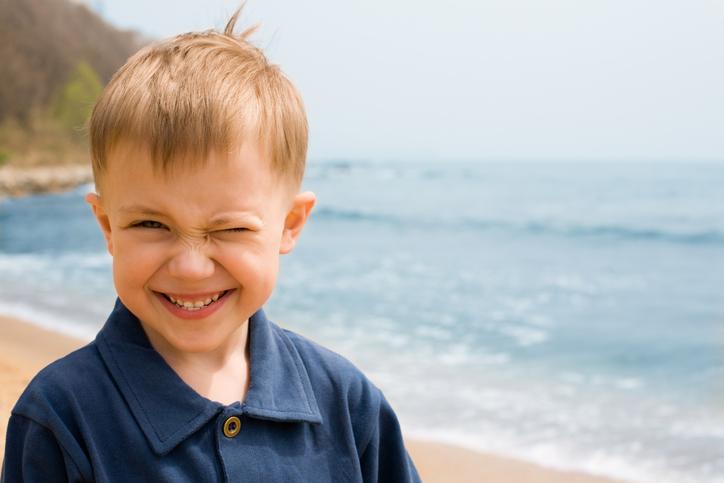Niño guiñando un ojo en la playa