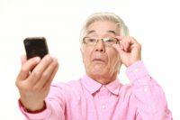 Hombre con gafas alejando el móvil para leer