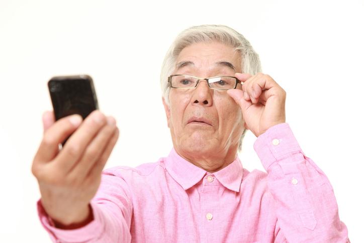 Hombre con camisa rosa aleja el móvil para verlo