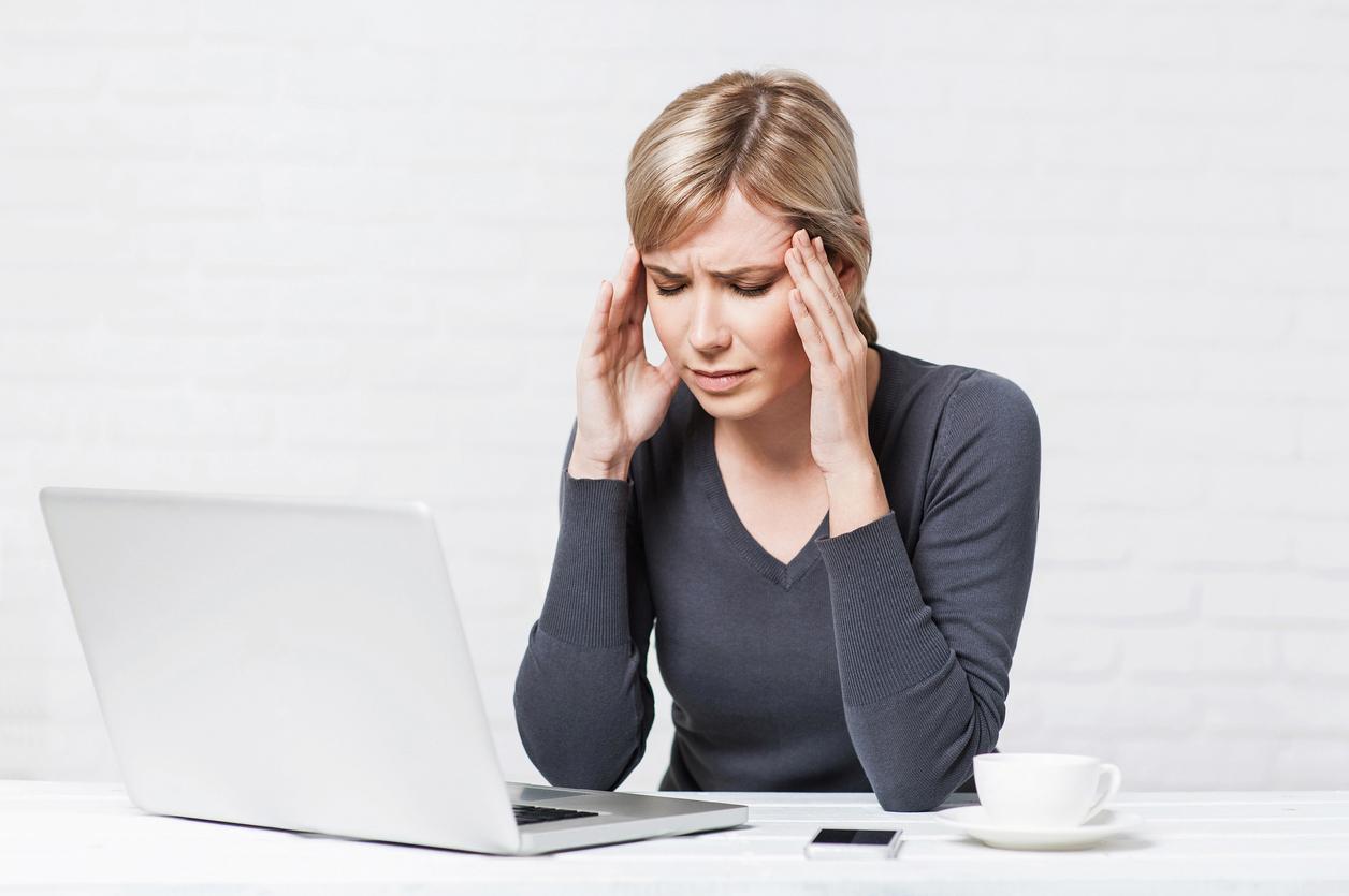 Mujer rubia con camiseta oscura frotándose las sienes