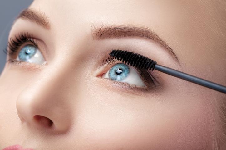 Mujer de ojos azules se maquilla las pestañas