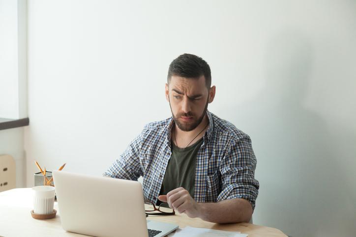 Hombre con camisa a cuadros mira el ordenador