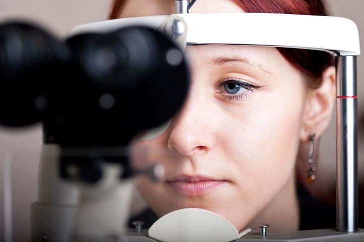Mujer pelirroja de ojos azules durante prueba oftalmológica