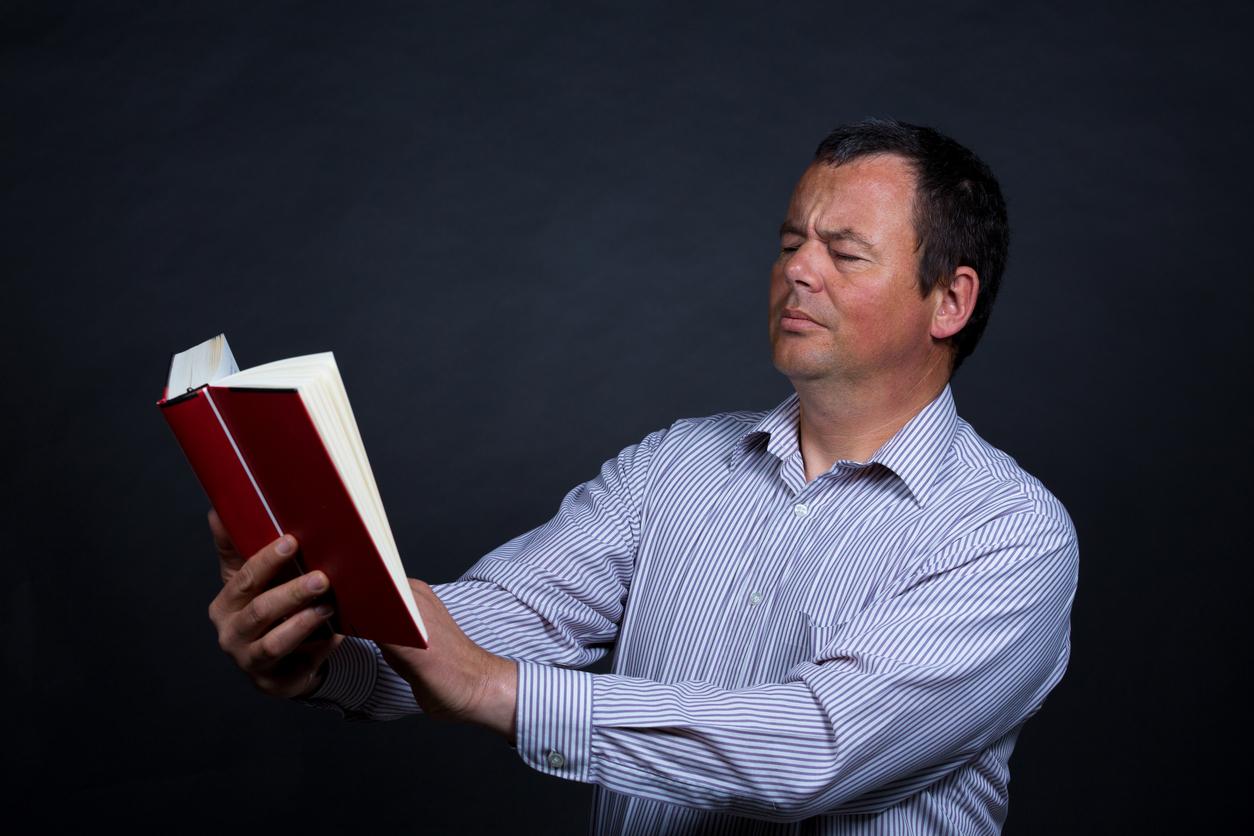 Hombre alejando un libro para poder leerlo