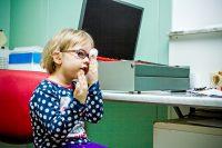 Niño rubio con gafas haciéndose una prueba oftalmológica