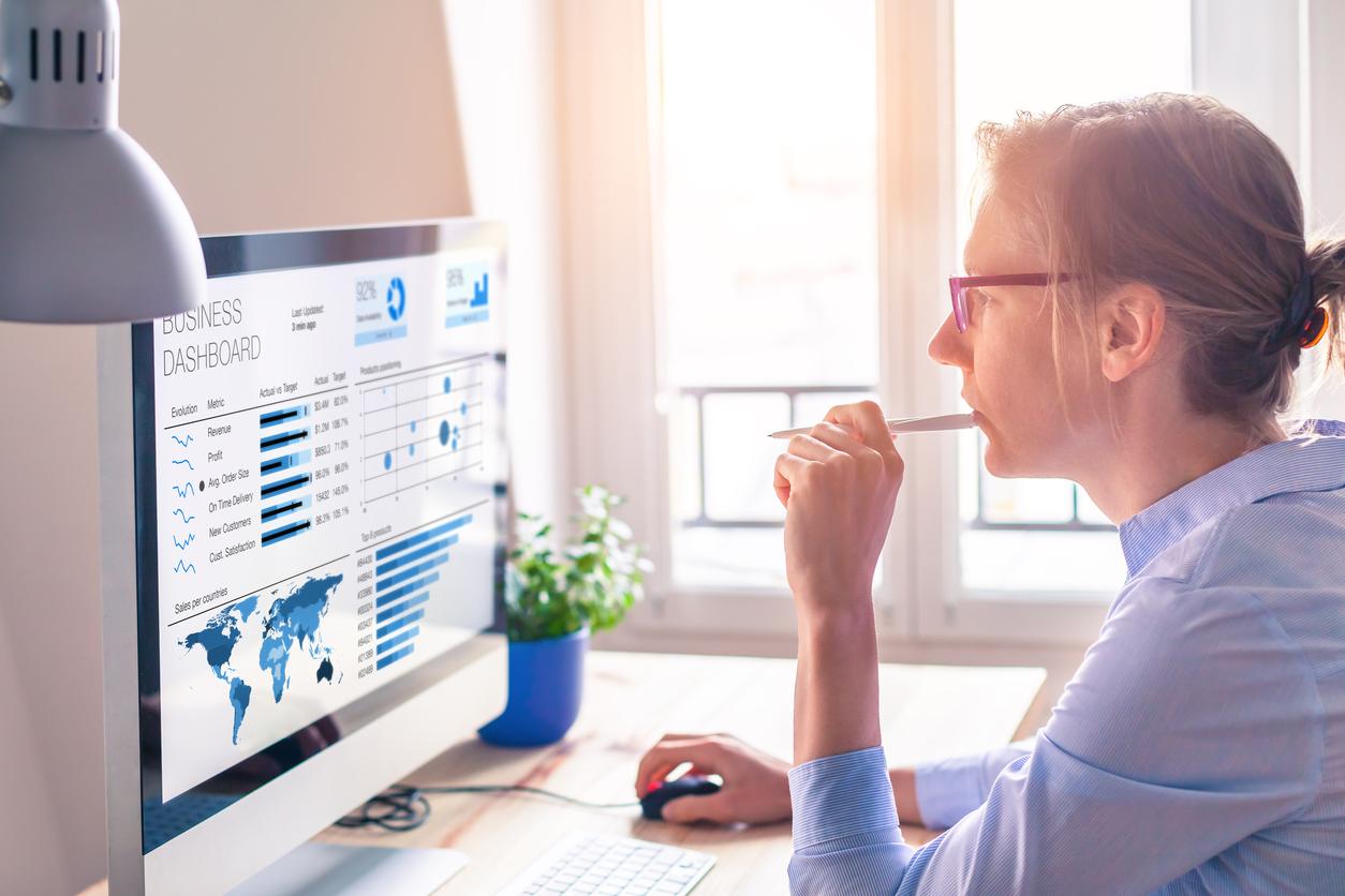 Mujer con camisa azul mirando una pantalla de ordenador