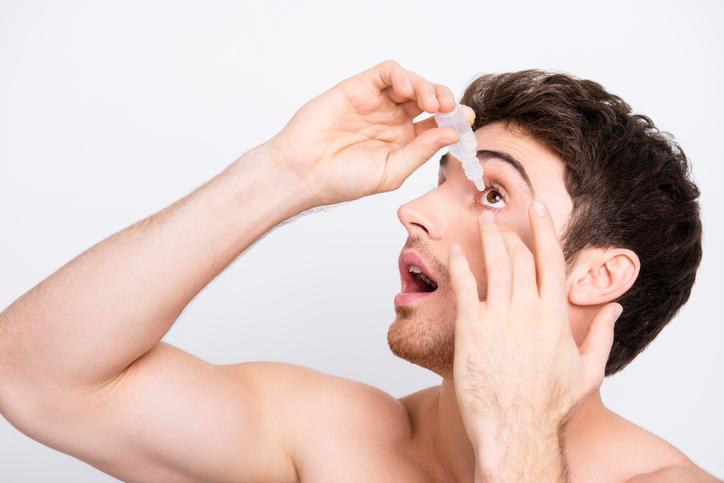 Hombre joven echándose gotas en un ojo
