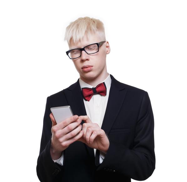 Hombre albino usando un teléfono