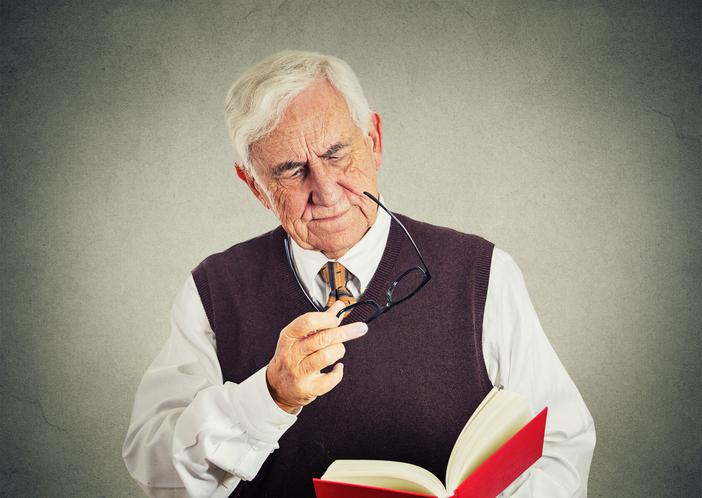 Hombre canoso con gafas en la mano y leyendo libro rojo