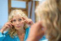 Mujer rubia mirándose los ojos en un espejo