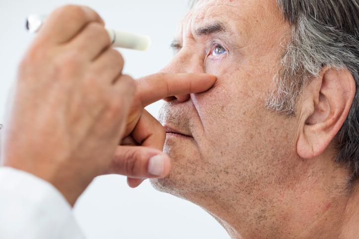 Oftalmólogo usando linterna para revisar a un hombre