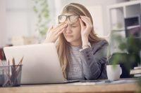 Mujer rubia se frota un ojo y se sube las gafas mientras trabaja en un ordenador