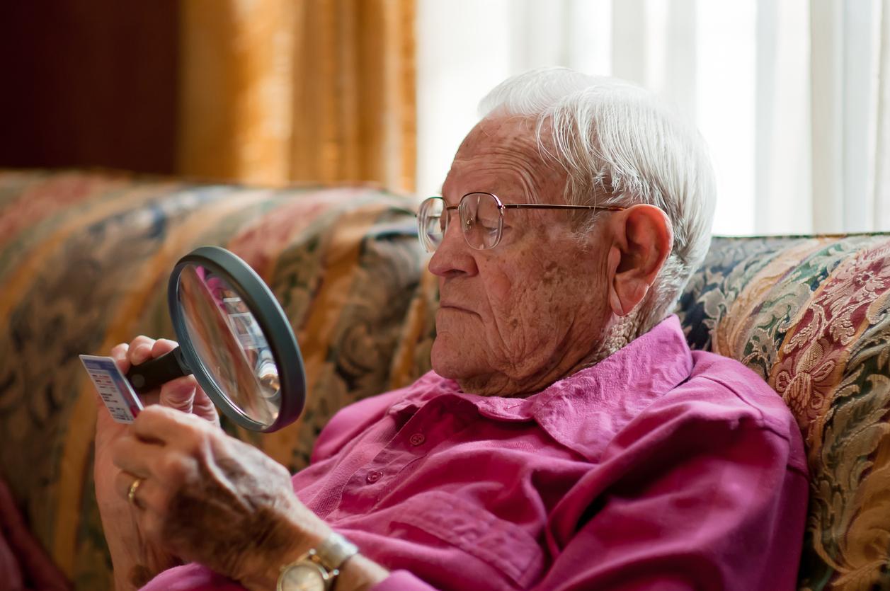 Hombre mayor con camisa rosa utilizando una lupa