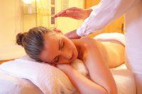 Mujer con moño tumbada en camilla durante un masaje