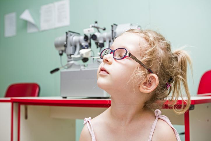 Niña rubia con gafas y ojos cerrados en consulta del oftalmólogo